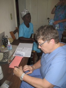 Nurse Pat fills out patient receipt for purchase of medications